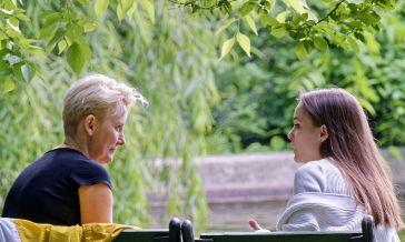 Kaksi ihmistä istuu puiden alla ja keskustelee.