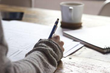Käsi, joka kirjoittaa kynällä paperille.